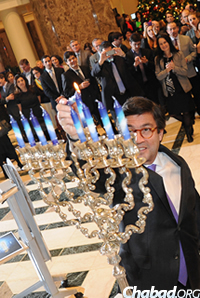 "Inter-American Development Bank president Luis Alberto Moreno lit the shamash (""attendant candle"") used by others to light the menorah at ""A World of Light."" (Photo: Len De Pas)"