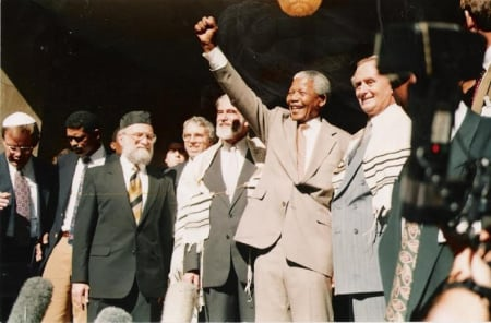 Nelson Mandela salutes the crowd at the Green and Sea Point Hebrew Congregation in Cape Town on a visit shortly after being elected South Africa's president in 1994. Joining Mandela, from left, are Rabbi Jack Steinhorn; Israel's ambassador to South Africa, Alon Liel; Chief Rabbi Cyril Harris; and Mervyn Smith, chairman of the South African Jewish Board of Deputies. (SA Rochlin Archives, SAJBD)