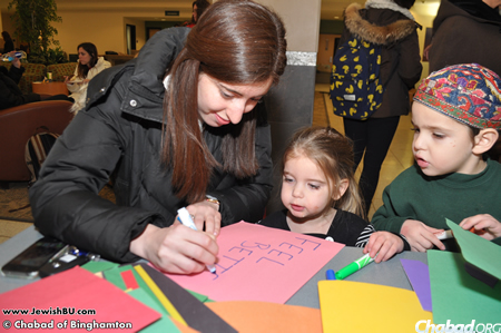 "Chabad student president Lucy Schwartz, left, makes ""Get Well"" cards for the children, along with Mushkah and Berkie Chein."