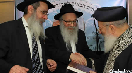Rabbi Yona Matusof, center, presents Rabbi Shlomo Moshe Amar with a book penned by his father, who was a close friend of Baba Sali, as Rabbi Yosef Posner looks on.