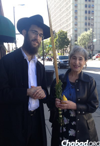 Rabbi Wolf shaking the lulav on Sukkot with Sarah Gabel