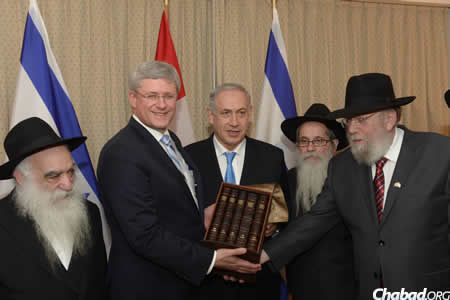 From left: Rabbi Berel Mockin, Prime Minister Stephen Harper, Prime Minister Benjamin Netanyahu, Rabbi Zalman A. Grossbaum and Rabbi Rabbi Yitzchok Wineberg, as Rabbi Wineberg presents Harper with a Chumash that includes commentaries of the Rebbe. (Photo: Amos Ben Gershom GPO)