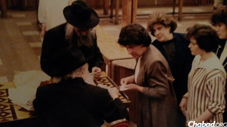 Mrs. Keny Deren, center, receiving a dollar and a blessing from the Rebbe.