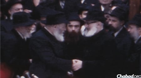 The Rebbe greets Rabbi Joseph B. Soloveitchik, who joined in the Yud Shevat farbrengen in 1980 in celebration of the Rebbe's 30th year of leadership. (Photo: Jewish Educational Media)