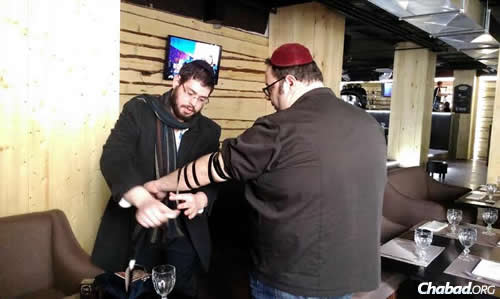 Rabbinical intern Dovid Katz helps a visitor to the Olympics put on tefillin.