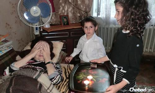 Children in Sumy help an elderly woman light Shabbat candles. (File photo)
