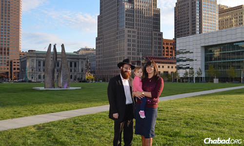 Rabbi Yossi and Chaya Freedman, co-directors of Chabad of Downtown Cleveland, with their daughter Nechama. The couple won one of the new Torahs donated by the Farkas family as part of a recent lottery.