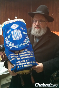 Rabbi Levy Wineberg with the Torah he picked up in New York and is now using in Johannesburg, South Africa. (Photo: Merkos Suite 302)