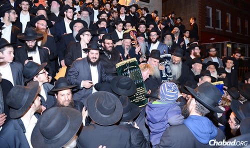 Brand-new Torahs were welcomed with a procession down Eastern Parkway in the Crown Heights neighborhood of Brooklyn, N.Y., with dancing, singing and a festive meal. Their donor, Leonardo Farkas, can be seen in the center; to his right is Rabbi Moshe Kotlarsky, vice chairman of Merkos L'Inyonei Chinuch, the educational arm of Chabad-Lubavitch. (Photo: Bentzi Sasson)