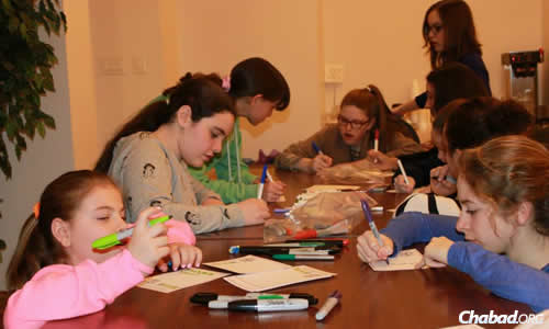 Girls at the Montreal Torah Center write notes to lone soldiers to be delivered on Purim. (Photo: Montreal Torah Center)