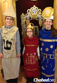 "The children of Rabbi Abba and Raizel Rubin of Chabad in Saratoga Springs, N.Y., try on costumes for this year's ""Israeli Purim."" From left are Moshe (mezuzah), Chana Malka (Torah) and Chaya (tzedakah box)."