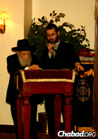 Reb Mottel speaking at Chabad of Midtown Manhattan with his grandson, Rabbi Levi Haskelevich.