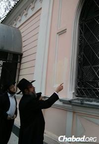 Chabad Rabbi Sholom Gotlieb, chief rabbi of Nikolayev, points to the damage.