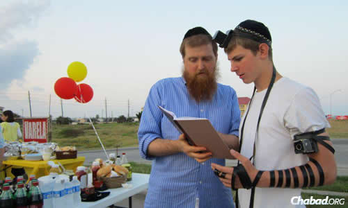 The rabbi helps Jacob Feldman don tefillin at an outdoor barbecue for the community.