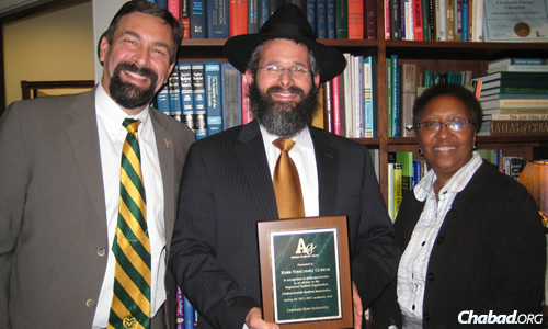 Gorelik with University President Tony Frank and Vice President Blanch Hughes at a previous awards ceremony, where he won recognition for his work as a faculty advisor for Chabad.