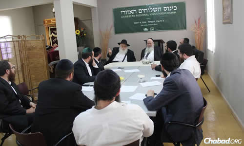 Rabbi Moshe Kotlarsky, seated in front of the podium, and to his left, Rabbi Shlomo Zarchi—dean and mashpia of the Central Yeshiva Tomchei Tmimim at Chabad-Lubavitch World Headquarters at 770 East Parkway in Brooklyn, N.Y.—share words of inspiration and guidance with the Caribbean rabbis during the multi-day conference.