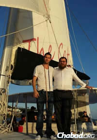 Rabbi Asher Federman assists a man putting on tefillin while boating off St. Thomas.