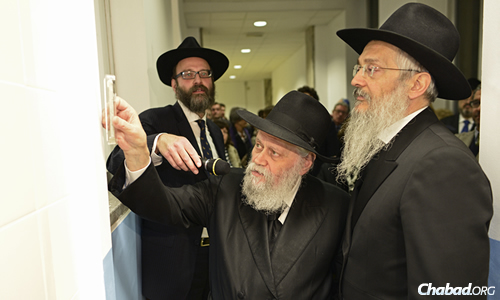 Rabbi Gershon M. Garelik, the first Chabad emissary to Italy who started his shlichus in 1958, affixes a mezuzah in the school, flanked by school director Rabbi Igal Hazan on the left and school dean Rabbi Avraham Hazan on the right.
