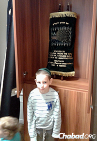 Mendy Kaminetzky, 6, stands in front of the Torah sent to Chabad-Lubavitch of Serbia, in Belgrade, co-directed by Yehoshua and Miri Kaminetzky.