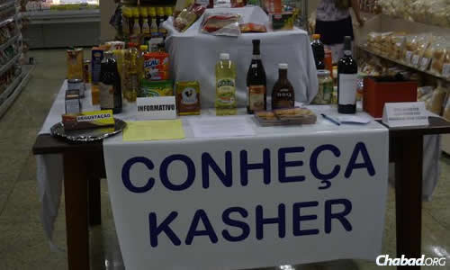 """A sign, """"Conheça Kasher (""""Know Kosher"""" in Portuguese),"""" advertises kosher week and products at a nearby store"""