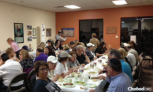 Guests enjoy kosher food at Chabad Houses near major tourist attractions in the United States and Canada. Here, a crowd dines together in Flagstaff.
