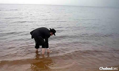 הרב אריה רייכמן מטביל כלים בנהר האמזונס.