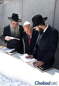 Safra at the Ohel in Queens, N.Y., with Rabbi Moshe Kotlarsky, left, and Rabbi Mendy Weitman