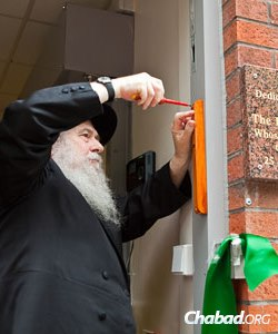 Rabbi Sudak affixing the mezuzah on a Chabad-run early-childhood center dedicated by the Gorman family in 2010.