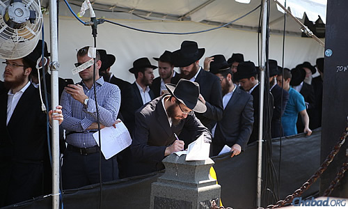 Jotting down some last-minute thoughts while waiting in line to enter the Ohel. (Photo: Chaim Perl)