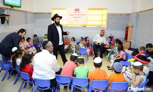 On Thursday, Rabbi Asher Pizem of Chabad of Sderot helped entertain children stuck inside all day because of the situation. Seated in front of him is Rabbi Prus of Kfar Chabad, Israel, and to Pizem's right, with the orange balloon hat, is CTVP staffer Rabbi Yossi Swerdlov. (Photo: Meir Alfasi)