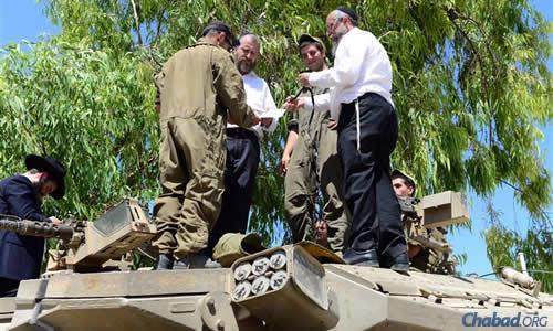 Swerdlov, left, and Prus aboard tanks to assist soldiers wrapping tefillin. (Photo: Meir Alfasi)