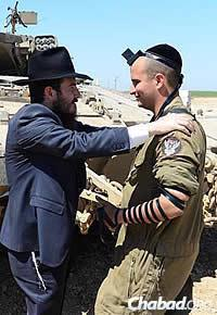 Cunin wraps tefillin with an Israeli soldier, surrounded by tanks and other military equipment. (Photo: Meir Alfasi)
