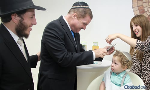 Rabbi Ahron and Chaya Blasberg, co-directors of Chabad of Aruba, with Aruban Prime Minister Mike Eman, who is snipping a lock of hair off Menny Blasberg at the 3-year-old's upsherin. (Photo: Mayo Stoppels Photography)