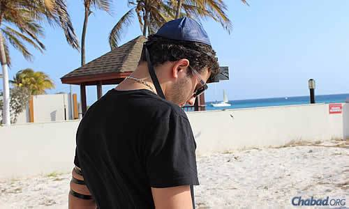 At a Lag BaOmer beach barbecue, resident Jon Atias performs the mitzvah of wrapping tefillin.