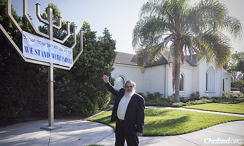 Rabbi Dovid Eliezrie, co-director of Congregation Beth Meir HaCohen, North County Chabad Center in Yorba Linda, Calif., with his wife Stella, attached a banner to the free-standing menorah on the synagogue grounds. (Photo: Clifford Lester)