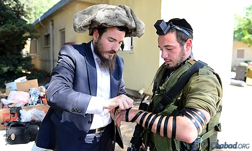 Rabbi Chaim Nochum Cunin, visiting Israel from Chabad West Coast Headquarters in Los Angeles, wrapped tefillin with a soldier earlier this week while temporarily relieving him of his head gear.