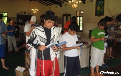Carmeli, left, as a teenager, leading prayers at Camp Gan Israel near his home in South Padre Island, Texas.