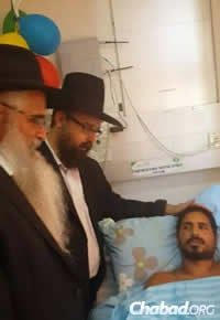 Rabbi Amitai Yemini, director of the Chabad Israel Center in Los Angeles, left, and Rabbi Menachem Kutner, director of the Chabad Terror Victims Project, visited with Mordechai Yemin, a wounded soldier. (Photo: CTVP)