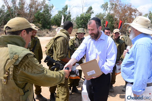 Rabbi Yossi Swerdlov, center, of the Chabad Terror Victims Project delivers packages to soldiers with Eli Katz, right, a volunteer from the United States. (Photo: Meir Dahan)
