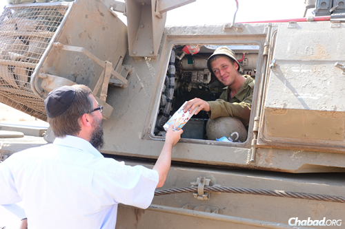 Rabbi Menachem Kutner of the Chabad Terror Victims Project hands a soldier at the Gaza border a much-appreciated treat. (Photo: Meir Dahan)