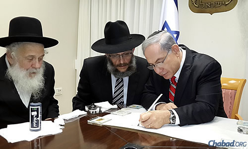 Netanyahu writes a letter in the first verse of the Torah using a special quill pen.