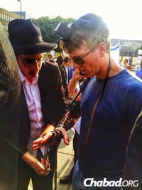 """John Flacks also wrapped tefillin. He reported: """"My first time putting on tefillin since my bar mitzvah, 36 years ago, yesterday at the rally. Baruch Hashem. Jerusalem and Israel will forever belong to the Jewish people."""""""