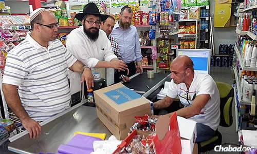 When the group heard of hungry families in Sderot, they went to the supermarket to buy and then distribute pasta, chicken and other foods. Kaplan is second from left; at the far right is Rabbi Yossi Swerdlov of the Chabad Terror Victims Project.