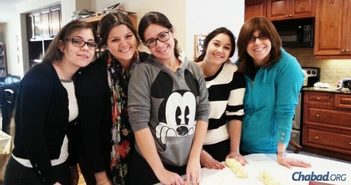 Students join Matti Banon, far right, in her kitchen, baking challah from scratch for Shabbat.