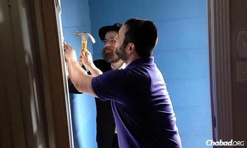 Rabbi Chaim Lazaroff of Houston, in the background, helps Brian Levinson affix his new mezuzah. (Photo Jillian Levinson)