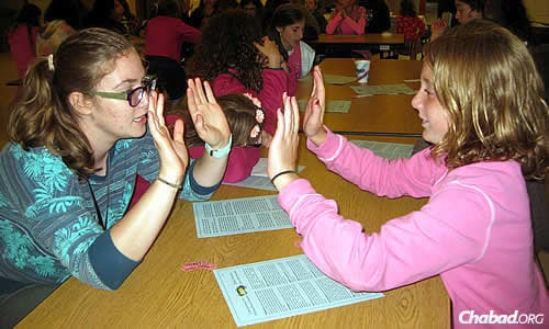 Emily Slezberg, right, lists her favorite camp activities as archery, the water trampoline, praying and listening to stories. The stories are a hit across the board.