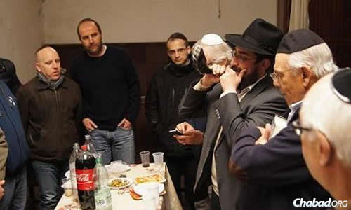 President Batlle and congregants listen intently as Shemtov blows the shofar, as is customary during the month of Elul.