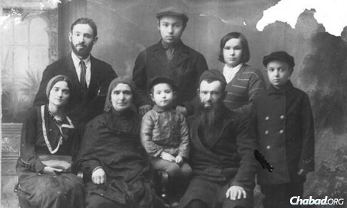 Rabbi Michoel and Sarah Katsenelenbogen with their children. Young Moshe is seated between his parents.