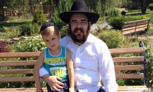 Rabbi Gopin with a child whose mother and grandmother were killed in an explosion in Lugansk.