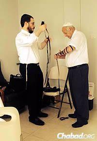 Rabbi Raskin wraps tefillin with Raymond Doweck's brother, Albert Doweck.